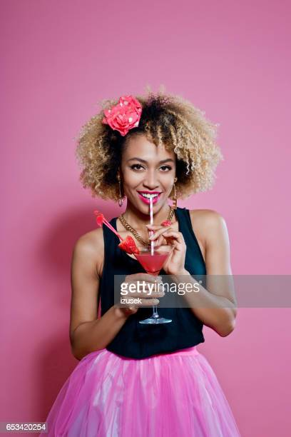 Happy afro woman drinking cocktail