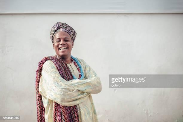 Afro-brasilianische glücklich in religiöser Tracht vor Wand