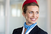 Cheerful flight attendant looking away. Portrait of happy flight assistant. Closeup face of mature woman airhostess wearing uniform and red cap with light blue scarf in airport.