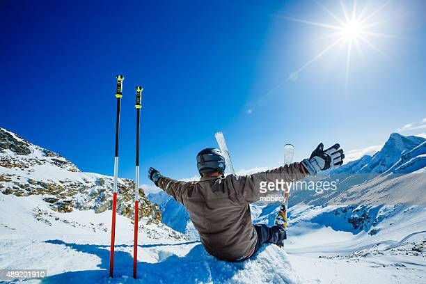 Happy alpine skier sitting on the edge