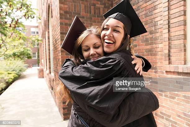 Happy American Mother Hugs Daughter Celebrating Graduation Day USA
