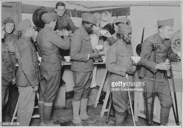 Happy American soldiers in uniform stand in line to receive bowls of chocolate and rolls at the American Red Cross canteen in Toulouse France 1917...