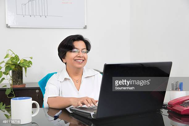 Happy and cheerful business woman working on her Laptop.