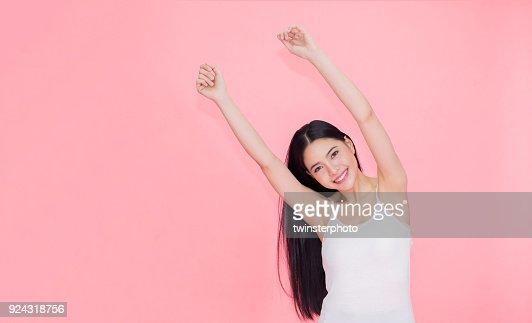 Gut gelaunt und fröhlich lächelnde asiatische 20er Jahre Frau Hände für positives Gefühl und Feier über rosa Hintergrund isoliert. : Stock-Foto