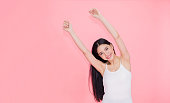 Happy and cheerful smiling Asian 20s woman raising hands up for positive feeling and celebration isolated over pink background