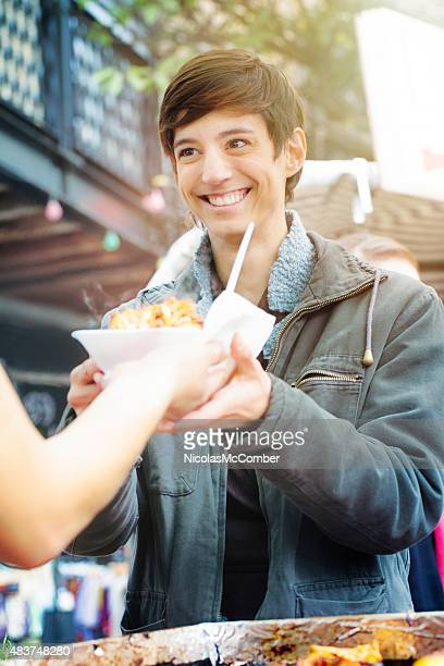Happy androgynous young British woman smiling receiving street food