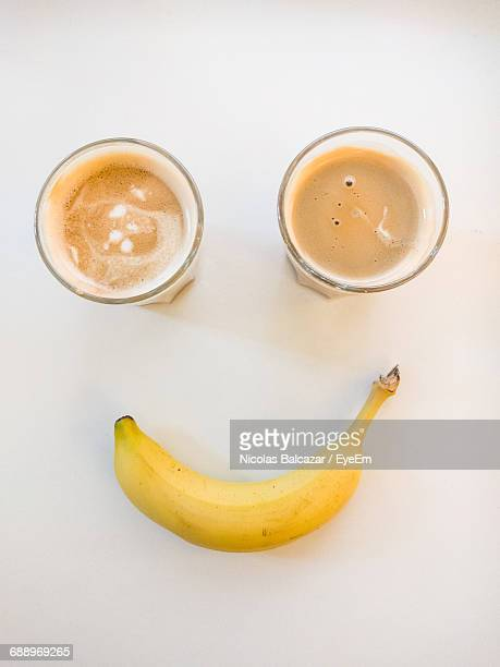 Happy Anthropomorphic Face Made From Banana And Coffee Glass On White Background