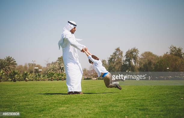 Happy Arab little boy and father having fun outdoors