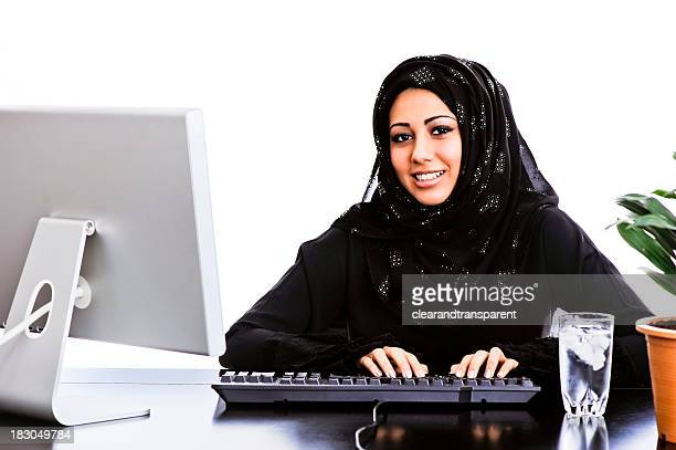 Happy Arabic girl working at her desk