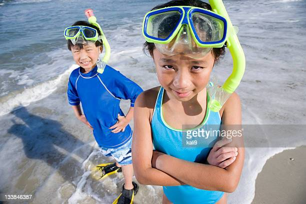 Happy Asian children with masks, snorkels and fins at beach