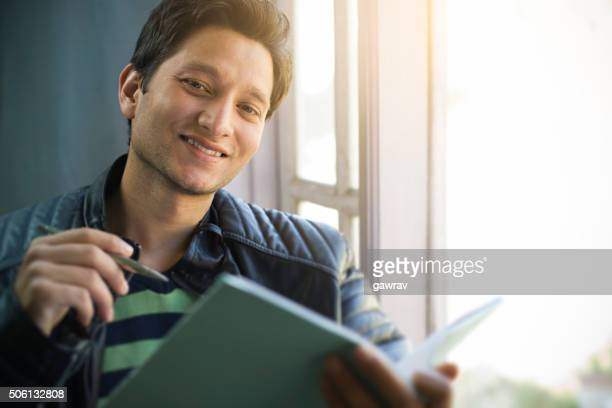 Happy, Asian, college student sitting near window with book pen.