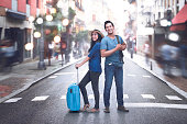 Happy asian couple with baggage enjoying vacations in the old town