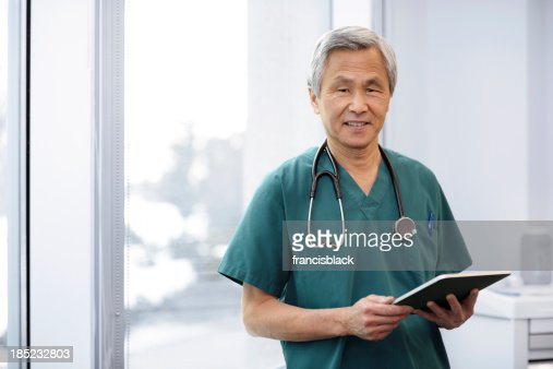 Happy Asian Doctor using a Tablet
