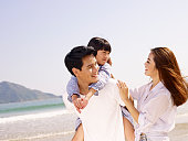 happy asian family vacationing on beach.