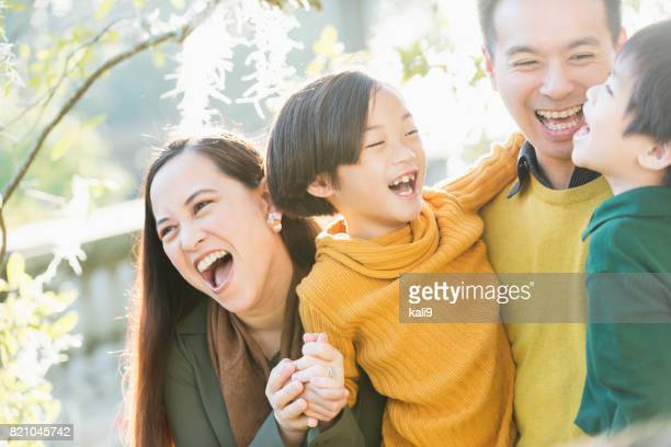 Happy Asian family with two children in park