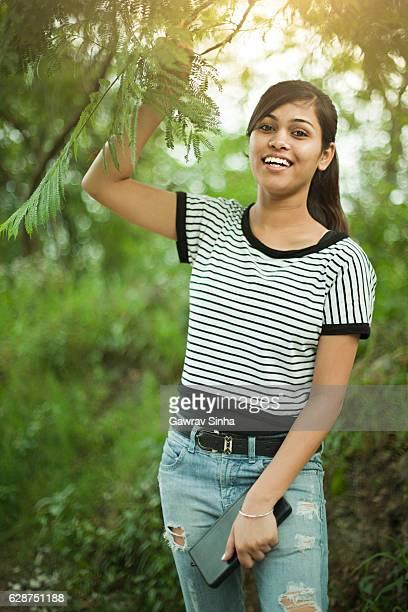 Heureuse fille asiatique tenant branche d'arbre en plein air dans la nature.