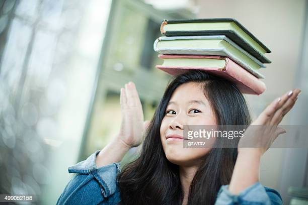 Happy Asian girl student balancing stack of books on head.