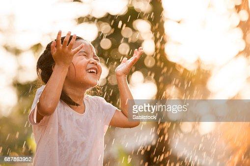 Feliz niña asiática divertirse para jugar con la lluvia : Foto de stock