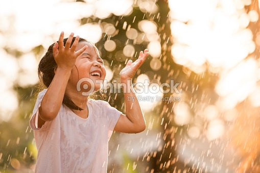 Happy asian little girl having fun to play with the rain : Foto de stock