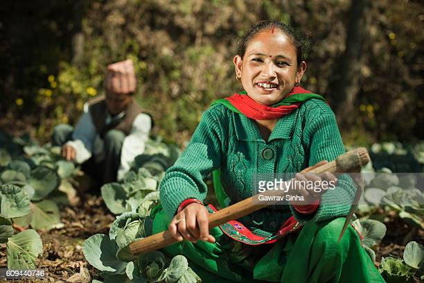 Happy Asian peasant woman in farm with hook.