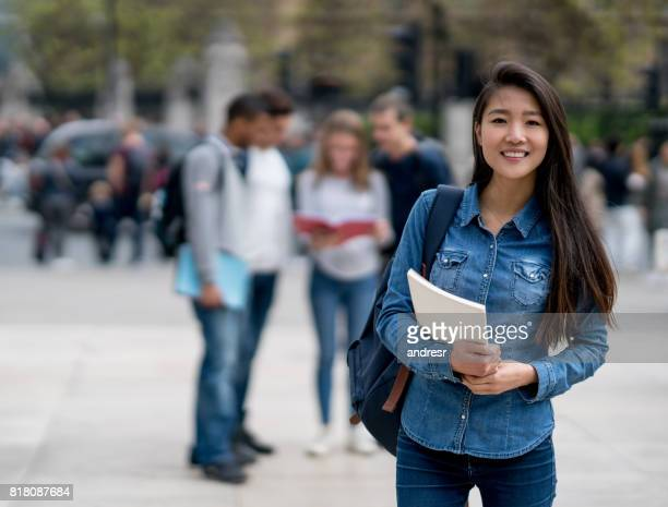 Happy Asian student on the street looking at the camera smiling