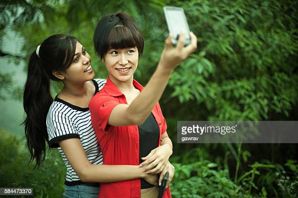 Happy Asian teenage friends taking selfie in nature.