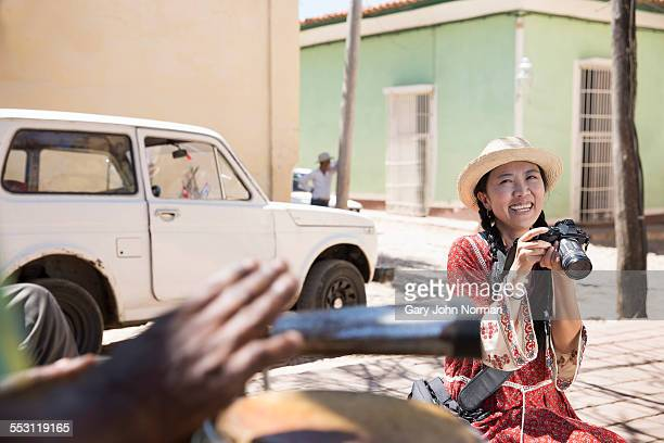 Happy asian tourist with her camera in the street.