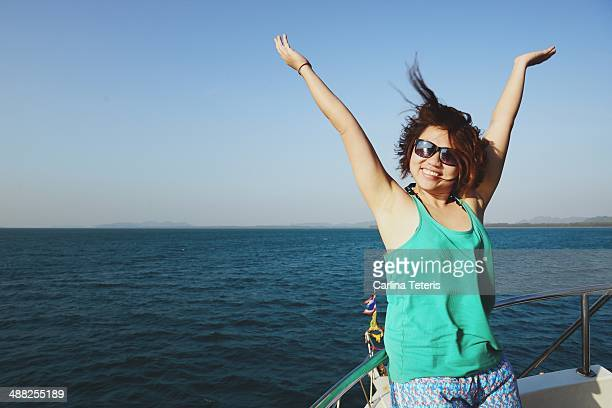 Happy Asian woman on a boat with her arms up