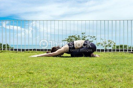 Heureuse femme asiatique portant yoga de pratique noir sport wear enfant  posent avec belle vue mer f6564f8ca4e