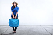 Happy asian woman with a suitcase posing against white wall background