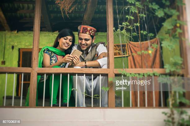 Happy Asian young couple using mobile phone.