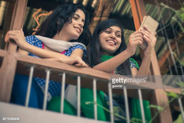 Happy Asian young women sharing mobile phone together.