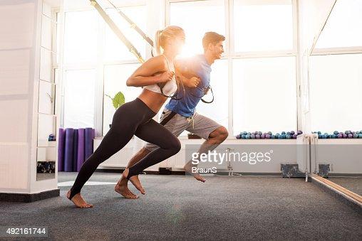 Happy athletes doing stretching exercises on Pilates equipment.
