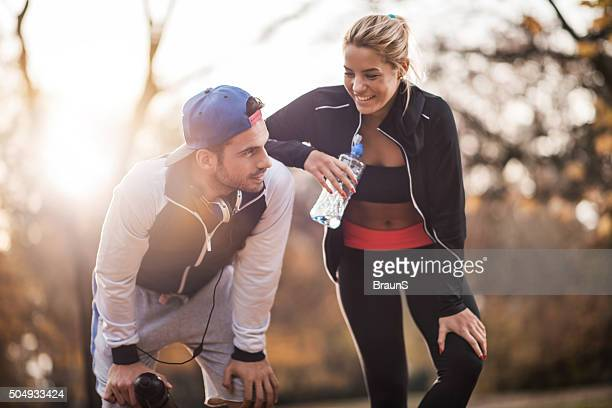 Happy athletes taking a break from exercising in nature.