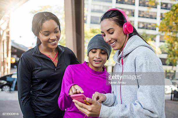 Happy athletes using smart phone on city street