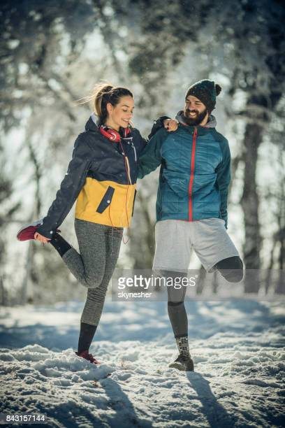 Happy athletic couple doing stretching exercises during winter day in nature.
