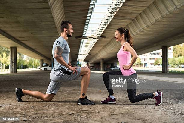 Happy athletic couple exercising lunges while looking at each other.