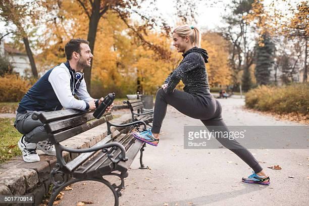 Heureux couple athlétique au repos après l'exercice dans le parc.