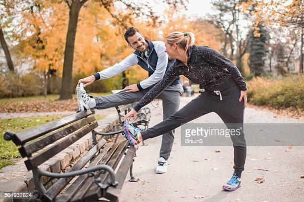 Happy athletic couple stretching their legs on a bench.