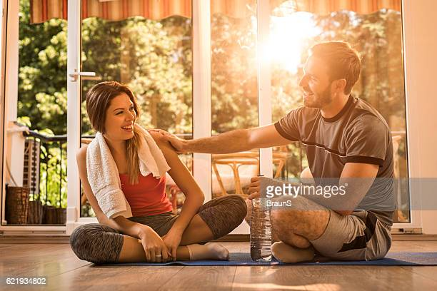Happy athletic couple talking to each other on a break.