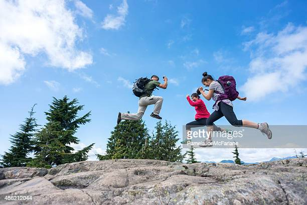 Happy, Athletic Hiking Family Jumping on Mountain Top with Backpacks