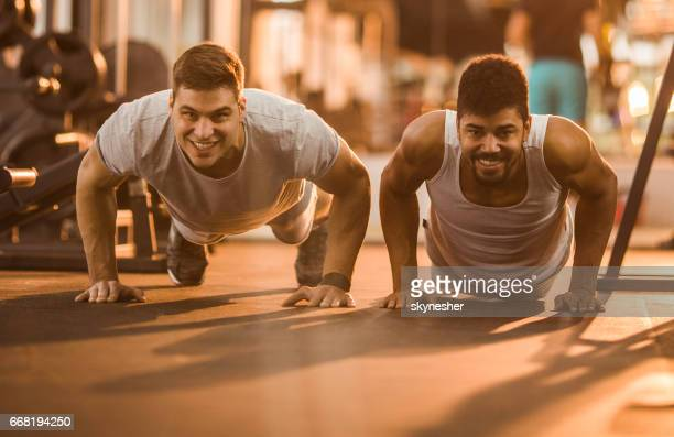 Happy athletic men exercising push-ups in a gym.
