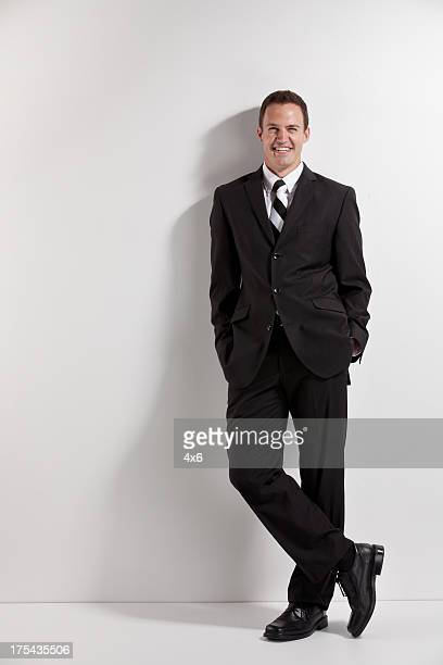 Happy attractive businessman leaning against a wall