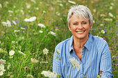 Happy attractive senior woman in a flowerfield in summerHappy attractive senior woman in a flowerfield in summer
