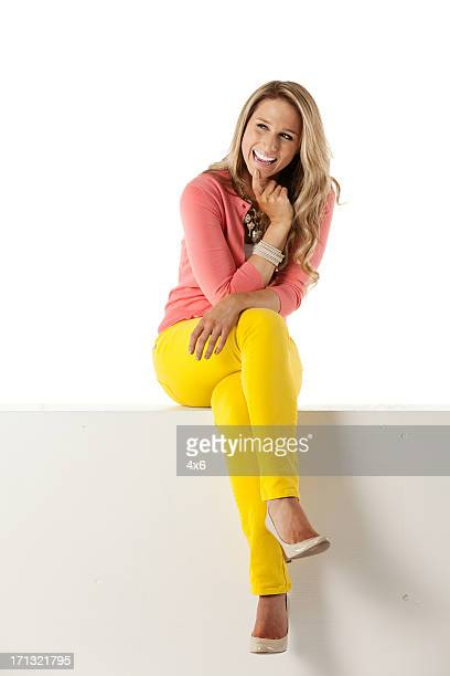 Happy attractive woman sitting on the ledge of a wall