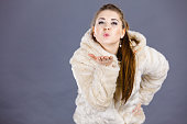 Happy attractive woman sending air kisses wearing light furry warm cozy coat with hood perfect for winter. Cold days fashion concept.