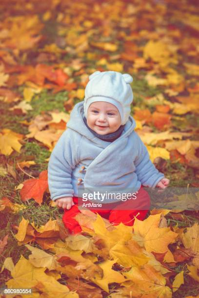 Happy baby boy in autumn