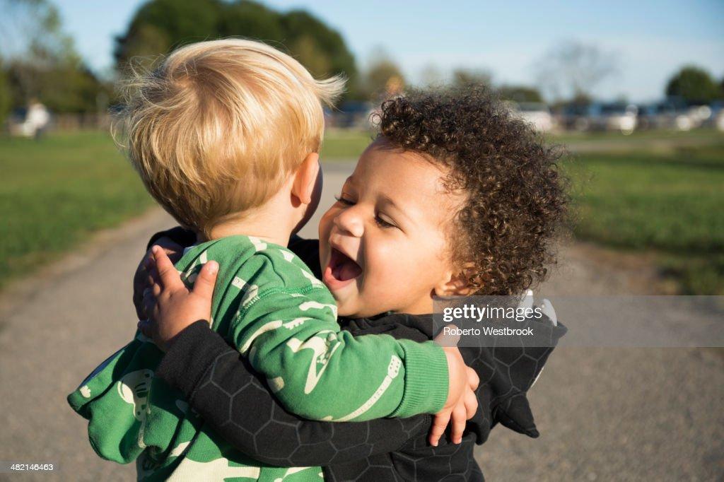 Happy baby boys hugging outdoors : Stock Photo