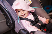 Portrait of a beautiful baby girl sitting on a car seat and smiling