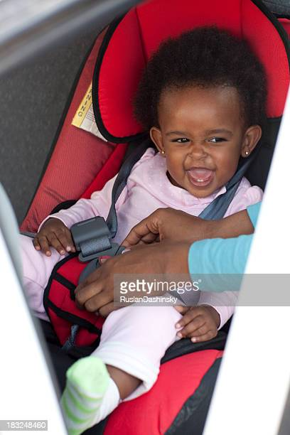 Happy baby girl  on a safety car  seat.
